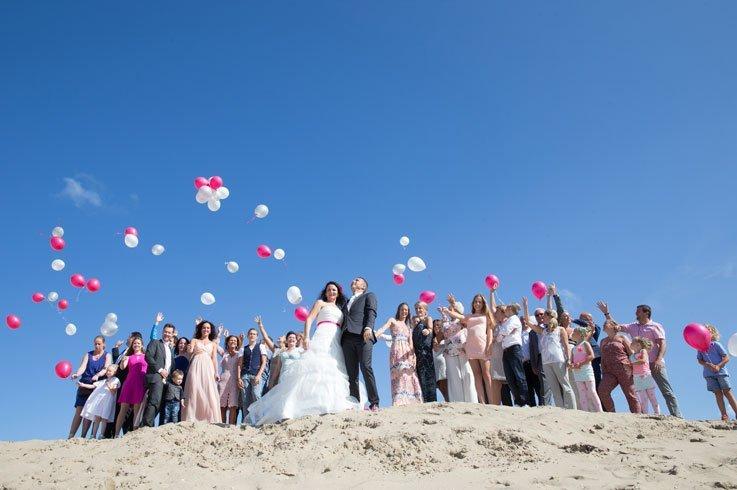 Een toffe groepsfoto op het strand tijdens een beach wedding