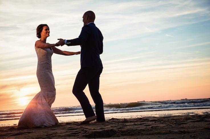 Als bruidspaar dansen in de branding