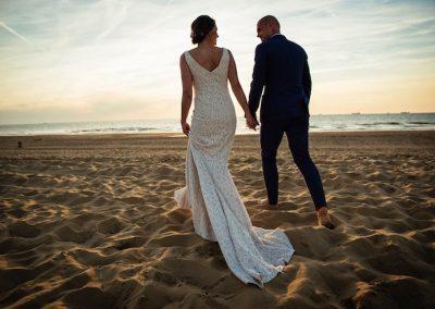 Bruidspaar op blote voeten in het zand