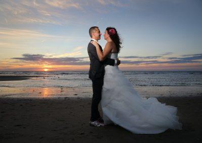 Trouwfoto's bij een ondergaande zon op het strand, romantiek ten top!