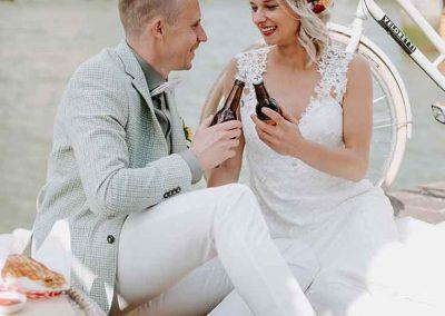 Een hip bruidspaar proost samen op het huwelijk aan de kade