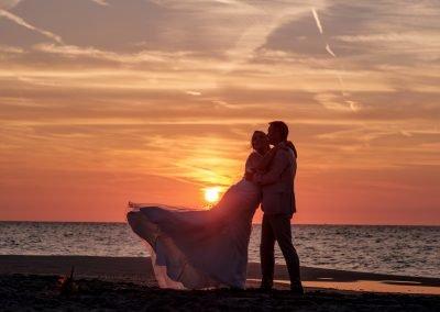 Foto's maken bruidspaar op het strand bij zonsondergang